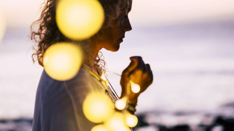 Emotional concept of hope and faith with adult woman and yellow bulb lights defocused - ocean and sunset in background - beautiful portrait for hoping conceptual image